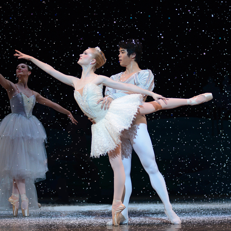 A female ballet dancer stands en pointe while a male ballet dancer holds her. Snow falls.